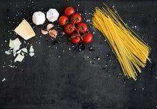 Marco de la comida Ingredientes de las pastas Cereza-tomates, pastas de los espaguetis, ajo, albahaca, parmesano y especias en gr Foto de archivo