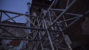Marco de la estructura de aluminio de la etapa enorme puesta afuera al lado de casa vieja almacen de metraje de vídeo