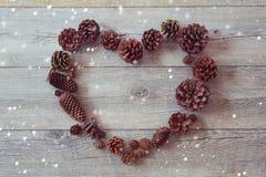 Marco de la forma del corazón del maíz del pino en fondo de madera Foto de archivo