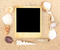 Marco de la foto de la vendimia y shell del mar en la arena Foto de archivo libre de regalías
