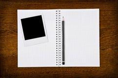 Marco de la foto en el cuaderno en blanco con el lápiz Fotos de archivo