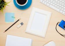 Marco de la foto en la tabla de la oficina con la libreta, el ordenador y la cámara Foto de archivo