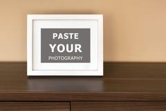 Marco de la foto en un estante de madera en la sala de estar Imágenes de archivo libres de regalías