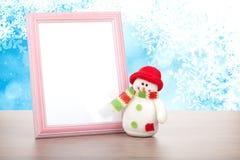 Marco de la foto y muñeco de nieve en blanco de la Navidad en la tabla de madera Imagen de archivo libre de regalías
