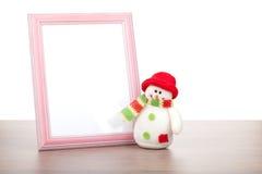 Marco de la foto y muñeco de nieve en blanco de la Navidad en la tabla de madera Imágenes de archivo libres de regalías