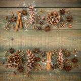 Marco de la frontera de la Navidad o del Año Nuevo con los conos, el anís y el canela del pino en fondo de madera Endecha plana,  Fotografía de archivo