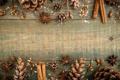 Marco de la frontera de la Navidad o del Año Nuevo con los conos del pino y canela en fondo de madera Endecha plana, visión super Imagen de archivo libre de regalías