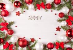 Marco de la luz de la Navidad adornado con las chucherías, los arcos y las ramas rojos y blancos del abeto Imágenes de archivo libres de regalías