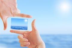 Marco de la mano y foto del paisaje marino stock de ilustración