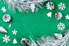 Marco de la Navidad con las ramas de árbol de abeto, conos del pino, ornamentos de plata en el fondo verde caliente, espacio de l Fotografía de archivo