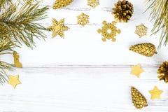Marco de la Navidad con las ramas de árbol de abeto, los conos del pino y los ornamentos de oro en el fondo de madera blanco, esp Foto de archivo