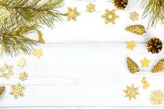 Marco de la Navidad con las ramas de árbol de abeto, los conos del pino y los ornamentos de oro en el fondo de madera blanco, esp Fotos de archivo libres de regalías
