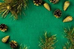 Marco de la Navidad con las ramas de árbol de abeto, los conos del pino y los ornamentos de oro en el fondo verde caliente, espac Imagen de archivo