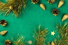Marco de la Navidad con las ramas de árbol de abeto, los conos del pino y los ornamentos de oro en el fondo verde caliente, espac Foto de archivo