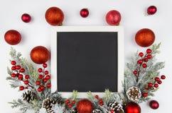Marco de la Navidad con las ramas de la baya de la Navidad adornadas con las bolas rojas Maqueta plano trandy Visión superior Fotografía de archivo libre de regalías