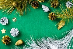 Marco de la Navidad con los ornamentos de las ramas de árbol de abeto, de los conos del pino, de plata y de oro en el fondo verde Imagen de archivo