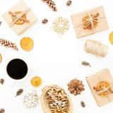 Marco de la Navidad de la decoración, de la caja de regalo, de la taza de café y de los conos del pino en el fondo blanco Día de  fotografía de archivo