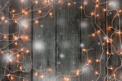 Marco de la Navidad en fondo de madera con nieve y luces Foto de archivo