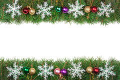 Marco de la Navidad hecho de las ramas del abeto adornadas con las bolas coloreadas y de los copos de nieve aislados en el fondo  Fotografía de archivo libre de regalías