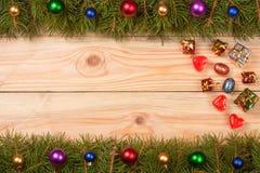 Marco de la Navidad hecho de las ramas del abeto adornadas con las bolas en un fondo de madera ligero Fotografía de archivo