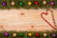 Marco de la Navidad hecho de las ramas del abeto adornadas con las bolas y el bastón de caramelo en un fondo de madera ligero Imágenes de archivo libres de regalías