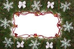 Marco de la Navidad hecho de las ramas del abeto adornadas con las campanas de los arcos y de los copos de nieve aislados en el f Imagen de archivo libre de regalías