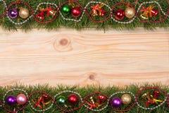 Marco de la Navidad hecho de las ramas del abeto adornadas con las gotas y las bolas de las campanas en un fondo de madera ligero Fotos de archivo libres de regalías