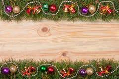 Marco de la Navidad hecho de las ramas del abeto adornadas con las gotas y las bolas de las campanas en un fondo de madera ligero Fotografía de archivo libre de regalías