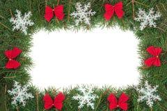 Marco de la Navidad hecho de las ramas del abeto adornadas con los arcos y de los copos de nieve aislados en el fondo blanco Imagenes de archivo