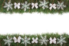 Marco de la Navidad hecho de las ramas del abeto adornadas con los arcos y de los copos de nieve aislados en el fondo blanco Fotografía de archivo