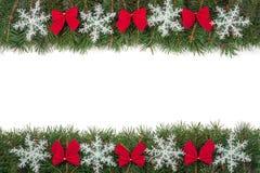 Marco de la Navidad hecho de las ramas del abeto adornadas con los arcos y de los copos de nieve aislados en el fondo blanco Fotos de archivo libres de regalías