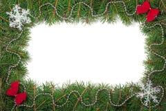 Marco de la Navidad hecho de las ramas del abeto adornadas con los arcos y de los copos de nieve aislados en el fondo blanco Foto de archivo libre de regalías