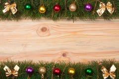 Marco de la Navidad hecho de las ramas del abeto adornadas con los arcos y las bolas de oro en un fondo de madera ligero Foto de archivo