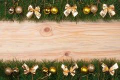 Marco de la Navidad hecho de las ramas del abeto adornadas con los arcos y las bolas de oro en un fondo de madera ligero Imagen de archivo libre de regalías