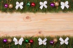 Marco de la Navidad hecho de las ramas del abeto adornadas con los arcos y las bolas del blanco en un fondo de madera ligero Fotografía de archivo