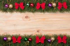 Marco de la Navidad hecho de las ramas del abeto adornadas con los arcos y las bolas del rojo en un fondo de madera ligero Imagen de archivo libre de regalías