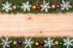 Marco de la Navidad hecho de las ramas del abeto adornadas con los copos de nieve y las bolas en un fondo de madera ligero Fotografía de archivo