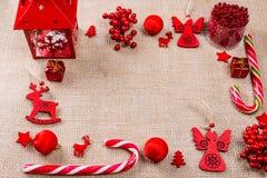 Marco de la Navidad hecho de juguetes, del caramelo, de regalos, de la linterna y de decoraciones rojos del Año Nuevo en la arpil fotos de archivo libres de regalías