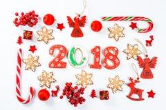 Marco de la Navidad hecho de juguetes rojos y de decoraciones del Año Nuevo con las galletas 2018 del pan de jengibre Fotografía de archivo libre de regalías