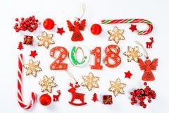 Marco de la Navidad hecho de juguetes rojos y de decoraciones del Año Nuevo con las galletas 2018 del pan de jengibre Imagen de archivo