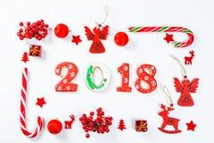 Marco de la Navidad hecho de juguetes rojos y de decoraciones del Año Nuevo con las galletas 2018 del pan de jengibre en el fondo Imagen de archivo