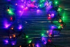 Marco de la Navidad de las luces de la guirnalda frontera elegante colorida en el bl Imagenes de archivo