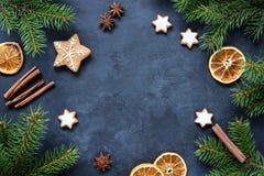 Marco de la Navidad o del Año Nuevo con el árbol de abeto, las especias, las galletas del pan de jengibre y los anillos anaranjad Imagenes de archivo
