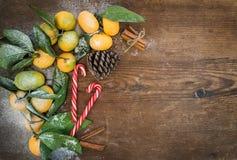 Marco de la Navidad o del Año Nuevo Mandarines frescos con las hojas, los palillos de canela, el cono del pino y los bastones de  Fotografía de archivo libre de regalías