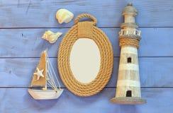 Marco de las cuerdas, faro y barco de navegación de madera en la tabla de madera concepto náutico de la forma de vida la plantill Fotografía de archivo libre de regalías