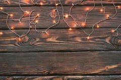 Marco de las luces de la Navidad en fondo de madera Imagen de archivo