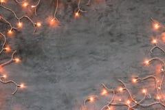 Marco de las luces de la Navidad en fondo de piedra gris oscuro Fotos de archivo libres de regalías