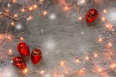 Marco de las luces de la Navidad en fondo de piedra gris oscuro con nieve Foto de archivo