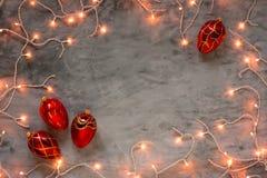 Marco de las luces de la Navidad en fondo de piedra oscuro con los ornamentos rojos Fotografía de archivo libre de regalías