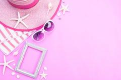 Marco de los accesorios de la playa, gafas de sol, estrellas de mar, sombrero de la playa y cáscara del mar en el fondo rosado pa fotos de archivo libres de regalías
